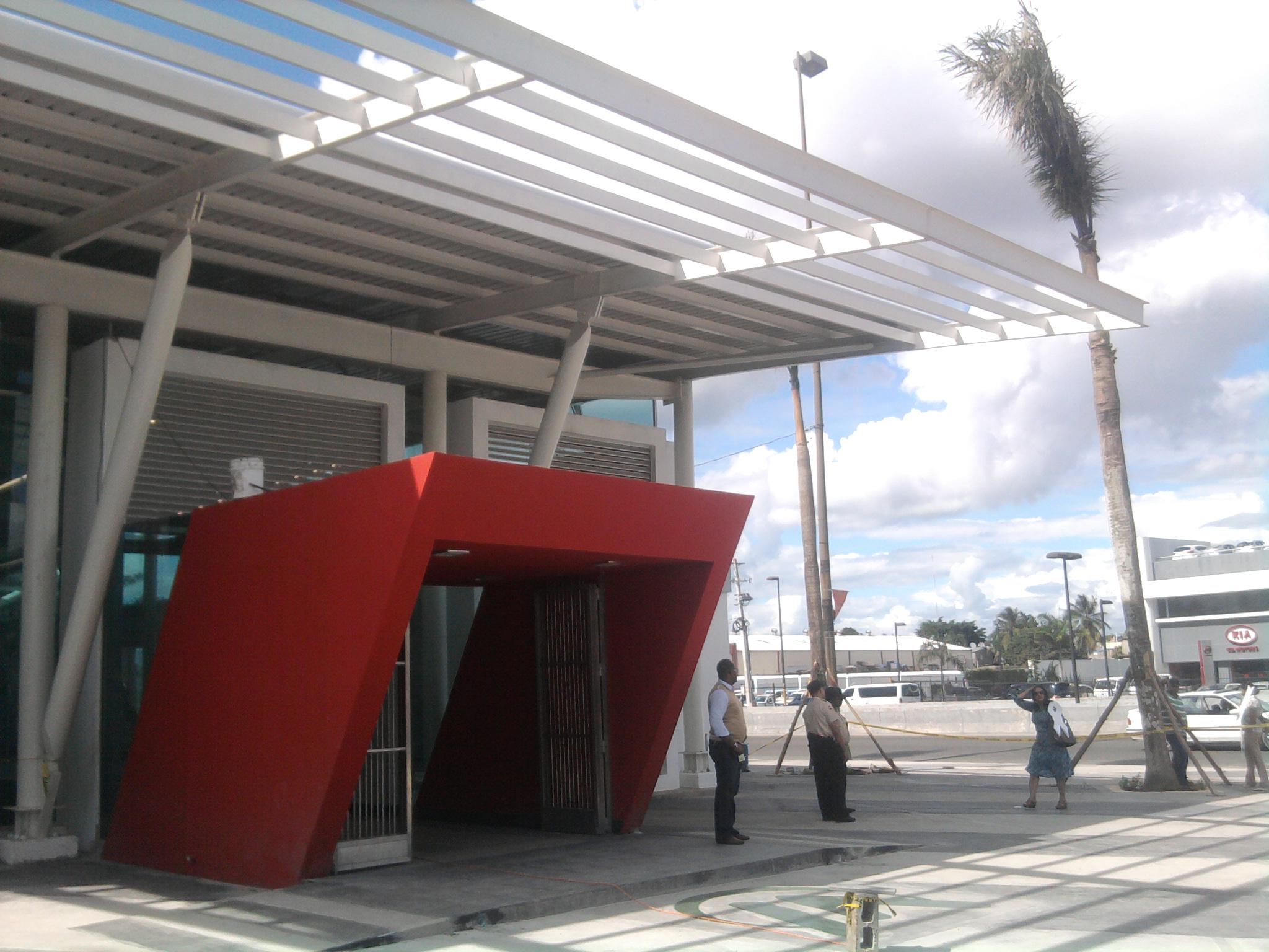 La estación 14 del metro de Santo Domingo, con un techo en estructura metálica y entrada color rojo.
